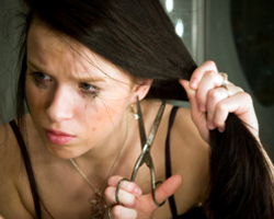 Teenage girl crying and cutting her hair