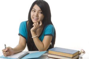 Asian student writing and thinking