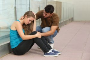 Beautiful teenager girl worried and a boy comforting her