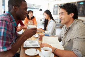Two Male Friends Meeting In Busy Coffee Shop