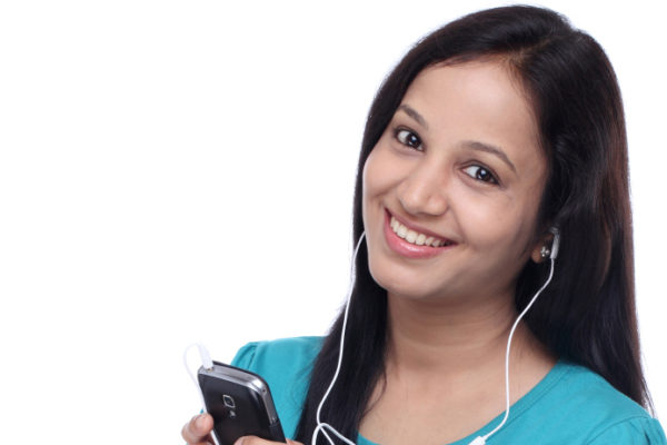 Beautiful young Indian woman listening music with earphones by smart phone