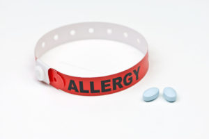 Allergy alert hospital wristband with blue medication tablets.